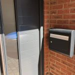 sole external post box mounted next to a modern front door