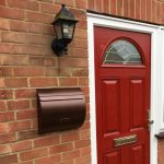 WA1 Wall Mounted External Post Box installed on a brick wall next to a red front door