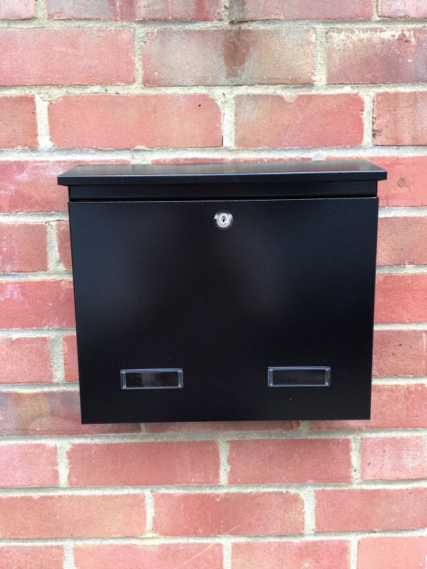 Wall Mounted Post Box Black mounted on a brick wall